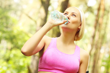 Fit woman drinking water in the forest