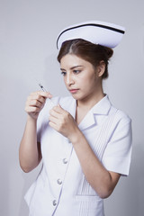 Young woman asian nurse attractive focus holding hypodermic syri