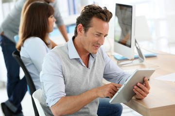 Attractive businessman in office using tablet
