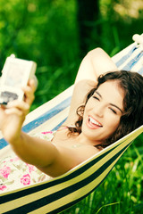Young woman in a hammock in garden doing snapshot.