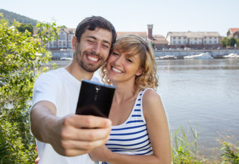 Laughing couple on the river taking a selfie
