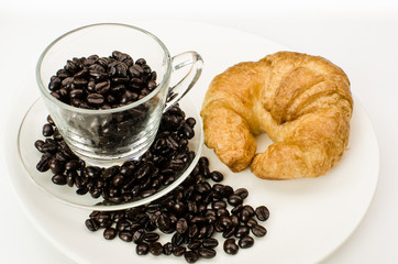 Cup of coffee beans with croissant