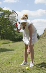 Female tennis player bending to collect ball