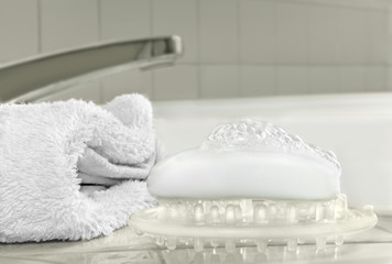 Bath accessories on porcelain tile,bar soap,bubbles,towel
