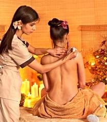 Woman getting thai herbal massage ball.