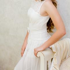 Woman in a white dress standing near white sofa