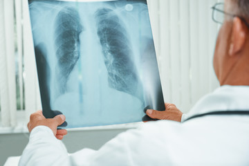 Unrecognizable older doctor examines x-ray image