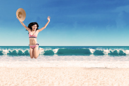 Excited woman leaping at beach 2