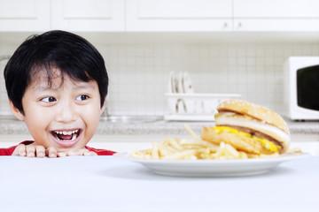 Hungry boy looking at beef burger