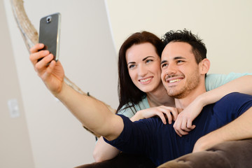 happy young couple making selfie at home with smart-phone