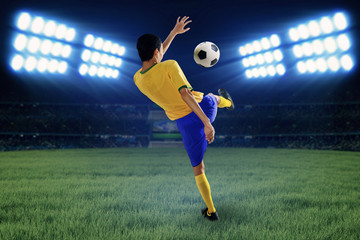 Soccer player kicking the ball at field