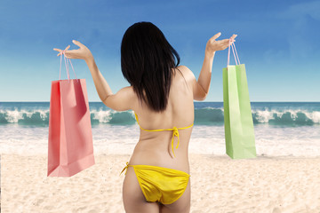 Woman holding shopping bag at beach