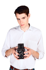 Young man with retro camera in hand isolated on white background