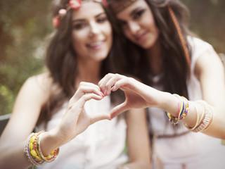 Boho girls showing heart shape from hands