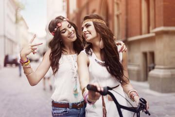 Boho girls walking alley of city