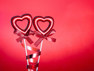 two red valentine hearts with bows against red background