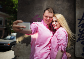 Happy couple taking photo of themselves or making selfie by smar