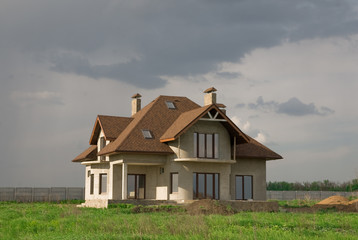 Tiled sunny cottage against cloudy grey sky