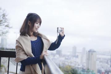 展望台から神戸の景色の写真を撮る笑顔の女性