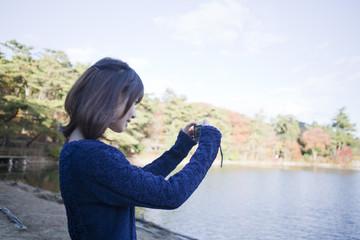 秋の紅葉の公園の池の前で写真を撮る笑顔の女性