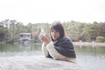 公園のテーブルでペットボトルを持つニットセーターを着た女性