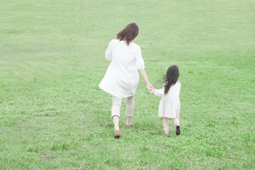 手を繋いで芝生を歩く母と子供