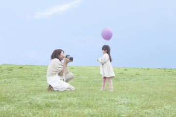 芝生で写真撮影をする母と子