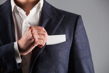 man who takes out business card from the pocket of suit,