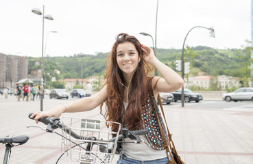 Smiling young woman with bicycle and heardphones in the street.