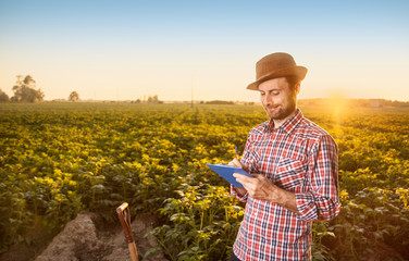 Happy farmer making notes in front of field