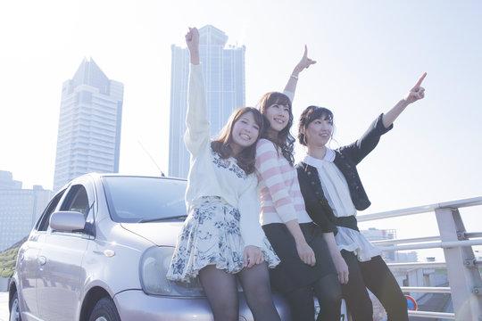 友達と車の前で楽しそうに手を上げる女性