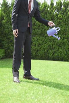 ジョウロで水やりをするビジネスマン
