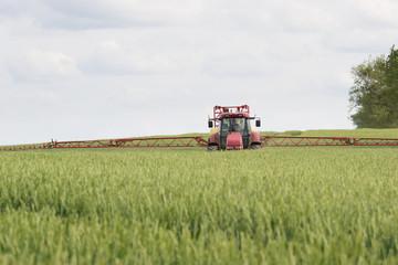 Traktor und Pestizide im Getreidefeld