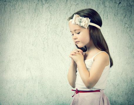 Portrait of little cute girl who prays or dreams