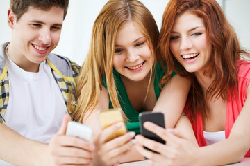 three smiling students with smartphone at school
