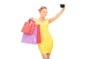 Classy girl with shopping bags taking a selfie