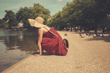 Young woman sitting by a lake in park