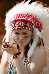 Young woman in headdress of American Indian smokes a pipe