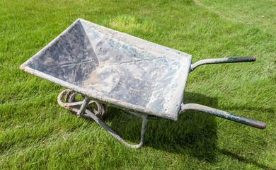 Grungy wheelbarrow on green grass in the garden