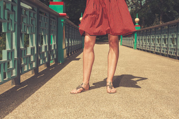 The legs of a young woman on a bridge