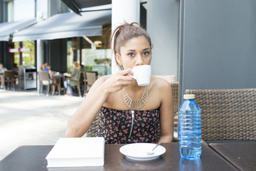 Beautiful woman drinking coffee in the terrace restaurant.