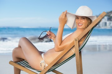 Smiling woman relaxing in deck chair on the beach