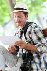Photo reporter in town using digital tablet