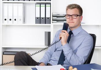 Mann sitzt entspannt mit Telefonhörer im Büro
