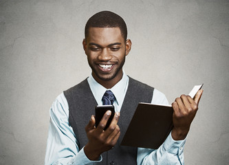 Businessman reading text message on mobile holding book simultan