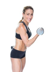 Female bodybuilder working out with large dumbbells smiling at c