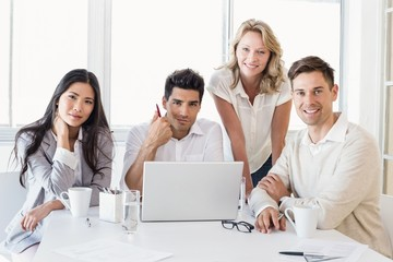 Casual business team having a meeting using laptop