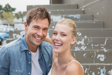 Hip young couple sitting on steps smiling at camera