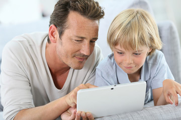 Man with little boy playing with digital tablet
