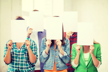 students covering faces with blank papers